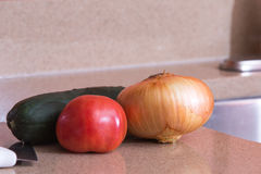 Fresh produce in the prep area. Kitchen onion pickle tomato cutting board knife stock photo