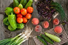 Overhead view of fresh fruits and vegetables in baskets on a wooden table royalty free stock photo