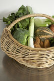 Fresh produce, seasonal vegetables in basket. Still life of vegetables on stainless steel bench in wicker basket Stock Photos