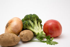 Fresh produce staged on a white background. Broccoli tomato onion royalty free stock images