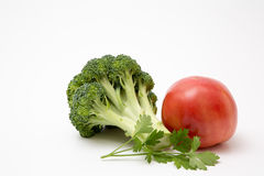 Fresh produce staged on a white background. Broccoli tomato onion garlic stock photo