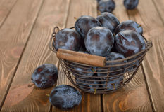 Fresh prunes. In a basket on a brown background Stock Image