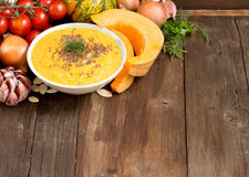 Fresh pumpkin soup. Fresh tomatoe soup with vegetables on a wooden table Stock Images