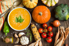 Fresh pumpkin soup and vegetables. On a wooden table Royalty Free Stock Photos
