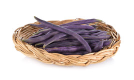 Fresh purple beans in rattan basket on white background Stock Photo