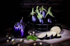 Fresh purple eggplant on an antique wooden table. Royalty Free Stock Image