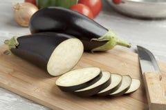 Fresh purple eggplants and slices. Fresh whole purple eggplants and slices on a cutting board Stock Images