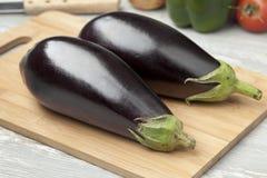 Fresh purple eggplants. Fresh whole purple eggplants on a cutting board Royalty Free Stock Photography