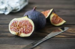 Fresh purple fig fruit and slices on wooden background royalty free stock images