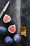 Fresh purple figs and table knife on old wooden background, top view Royalty Free Stock Photo