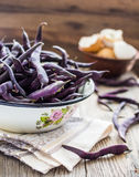 Fresh purple string beans on a gray wooden table,clean eating Stock Photos