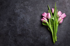 Fresh purple tulip flowers. On dark stone table. Top view with copy space Stock Photo