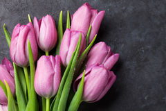 Fresh purple tulip flowers. On dark stone table. Top view with copy space Royalty Free Stock Images