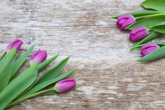 Fresh purple tulip flowers on wooden table Royalty Free Stock Photos