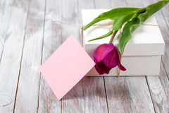 Fresh purple tulips bouquet and gift box on wooden background. Space for text. Fresh purple tulips bouquet and gift box on the wooden background. Space for text Royalty Free Stock Images