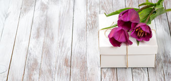 Fresh purple tulips bouquet and gift box on wooden background. Space for text. Fresh purple tulips bouquet and gift box on the wooden background. Space for text Stock Photography