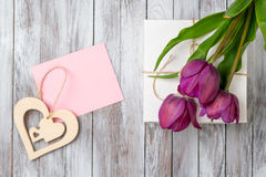 Fresh purple tulips bouquet and gift box on wooden background. Space for text. Decorative heart. Fresh purple tulips bouquet and gift box on the wooden Stock Photography