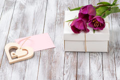 Fresh purple tulips bouquet and gift box on wooden background. Space for text. Decorative heart. Stock Photo