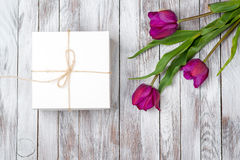 Fresh purple tulips bouquet and gift box on wooden background. Space for text. Top view. Fresh purple tulips bouquet and gift box on the wooden background Stock Photos