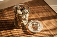 Fresh quail eggs. Quail eggs in a decorative glass jar on the table in the sun Stock Photo