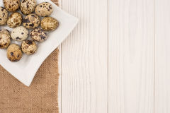 Fresh quail eggs in a white plate. On a wooden background Royalty Free Stock Photography