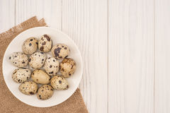 Fresh quail eggs in a white plate. On a wooden background Royalty Free Stock Image