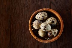 Fresh quail eggs in a wooden bowl on a dark wooden background, top view, close-up. Some copy space for your inscription. Textured background emphesize the royalty free stock photography