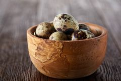 Fresh quail eggs in a wooden bowl on a dark wooden background, top view, close-up. Some copy space for your inscription. Textured background emphesize the stock photography