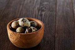 Fresh quail eggs in a wooden bowl on a dark wooden background, top view, close-up. Some copy space for your inscription. Textured background emphesize the royalty free stock image