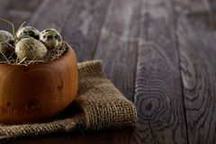Fresh quail eggs in a wooden bowl on a dark wooden background, top view, close-up. Some copy space for your inscription. Textured background emphesize the Stock Photos