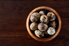 Fresh quail eggs in a wooden bowl on a dark wooden background, top view, close-up. Some copy space for your inscription. Textured background emphesize the Stock Photo