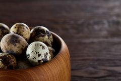 Fresh quail eggs in a wooden bowl on a dark wooden background, top view, close-up. Some copy space for your inscription. Textured background emphesize the Royalty Free Stock Photo