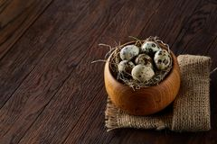 Fresh quail eggs in a wooden bowl on a dark wooden background, top view, close-up. Some copy space for your inscription. Textured background emphesize the stock image