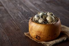 Fresh quail eggs in a wooden bowl on a homespun napkin over dark wooden background, top view, close-up. Blurred. Some copy space for your inscription. Textured Royalty Free Stock Image