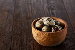 Fresh quail eggs in a wooden bowl on a homespun napkin over dark wooden background, top view, close-up. Blurred. Some copy space for your inscription. Textured Stock Images