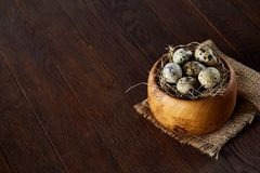 Fresh quail eggs in a wooden bowl on a homespun napkin over dark wooden background, top view, close-up. Some copy space for your inscription. Textured Stock Photos