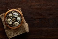 Fresh quail eggs in a wooden bowl on a homespun napkin over dark wooden background, top view, close-up. Some copy space for your inscription. Textured Stock Photo