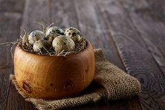 Fresh quail eggs in a wooden bowl on a homespun napkin over dark wooden background, top view, close-up. Some copy space for your inscription. Textured Royalty Free Stock Images