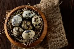 Fresh quail eggs in a wooden bowl on a homespun napkin over dark wooden background, top view, close-up. Some copy space for your inscription. Textured Stock Images