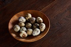 Fresh quail eggs in a wooden plate on a dark wooden background, top view, close-up. Some copy space for your inscription. Textured background emphesize the Royalty Free Stock Images