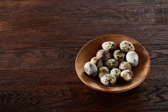 Fresh quail eggs in a wooden plate on a dark wooden background, top view, close-up. Some copy space for your inscription. Textured background emphesize the royalty free stock image