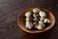 Fresh quail eggs in a wooden plate on a dark wooden background, top view, close-up. Some copy space for your inscription. Textured background emphesize the Royalty Free Stock Photos