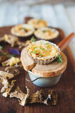 Fresh Quiche lorraine. Close-up of Quiche lorraine with thyme and dried mushrooms on the old wooden board Royalty Free Stock Photo