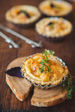 Fresh Quiche lorraine. Close-up of Quiche lorraine with fresh thyme on the old wooden board Stock Photo