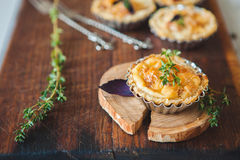 Fresh Quiche lorraine. Close-up of Quiche lorraine with fresh thyme on the old wooden board Royalty Free Stock Image