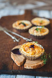 Fresh Quiche lorraine. In portion holder on the old wooden board Royalty Free Stock Photos
