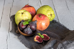 Fresh quinces and pomegranates. On wooden table with napkin Stock Photos