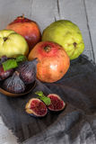Fresh quinces and pomegranates. On wooden table with napkin Stock Image