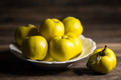 Fresh quinces. On the wooden table Stock Photos