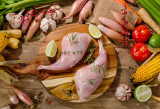 Fresh rabbit legs. With fresh vegetables on wooden board. Top view Stock Image